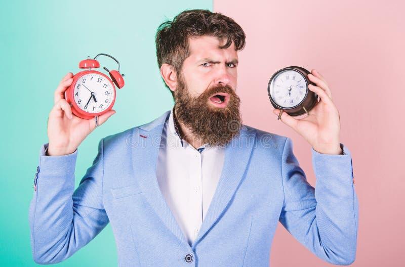 Kerel ongeschoren in verwarring gebracht gezicht die problemen met veranderende tijd hebben Tijdzone Doet veranderende klok knoei stock foto's