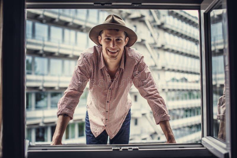 Kerel in roze overhemd die door venster kijken stock fotografie