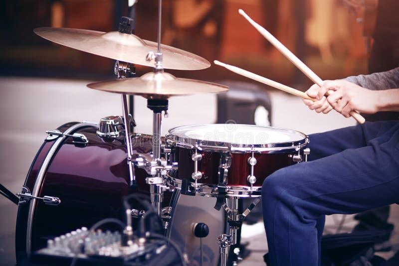 Kerel speelritme op een rood drumstel met trommelstokken stock fotografie