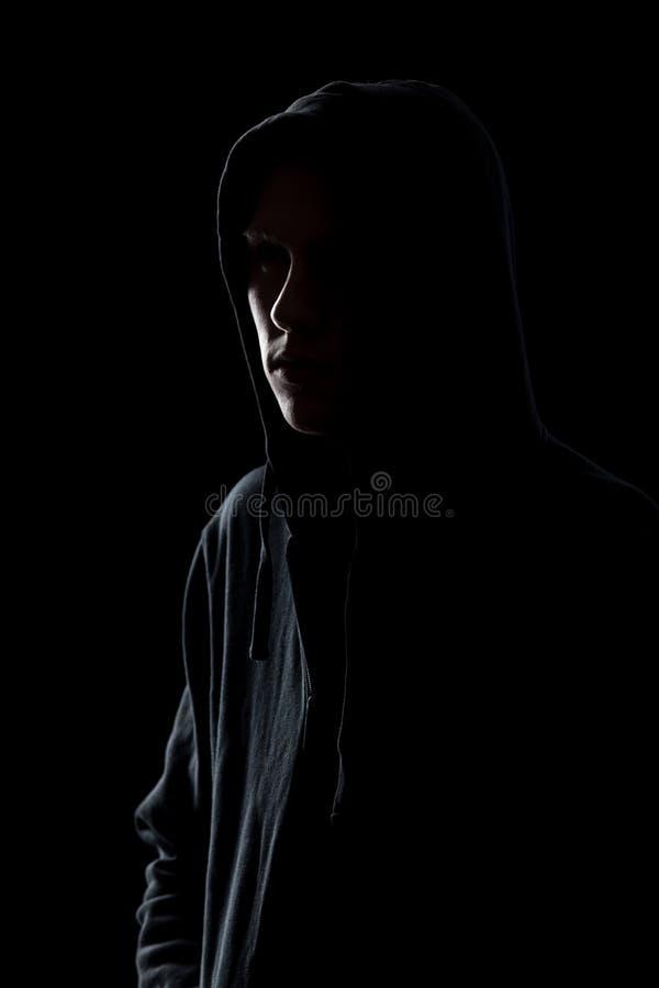 Kerel in sweatshirt met een kap in dark stock fotografie