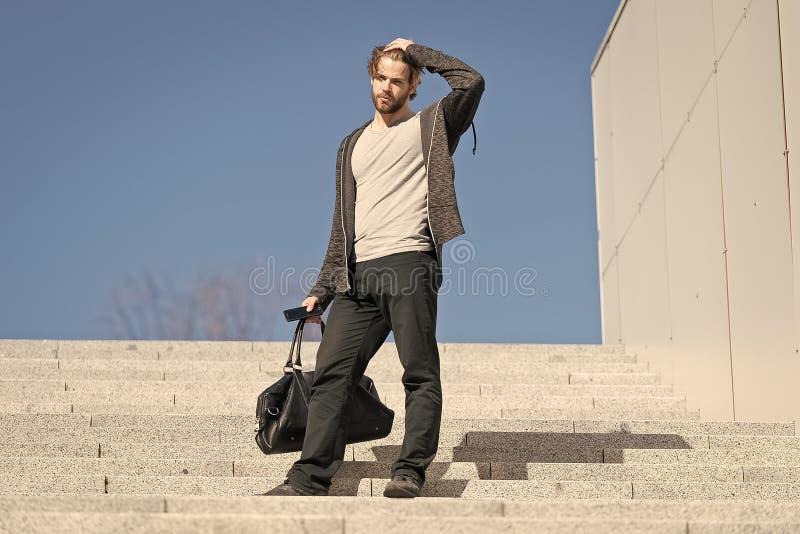Kerel in vrijetijdskledingstribune op treden op blauwe hemel, manier Mens met zak, smartphone op stappen op zonnige openlucht Kla royalty-vrije stock foto