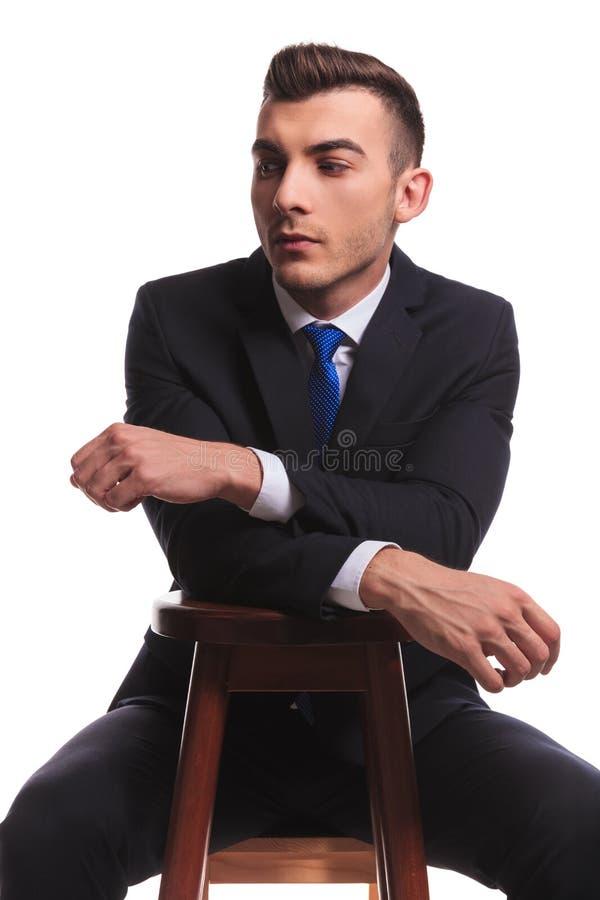 Kerel in zwart die kostuum met handen op een stoel worden gekruist stock fotografie