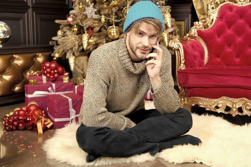 Kerelbespreking op mobiele telefoon bij Kerstboom stock afbeelding