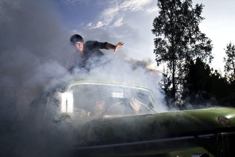 Kerels in autohoogtepunt van rook stock fotografie