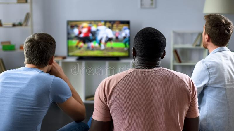 Kerels die actief Amerikaans voetbalteam, liefde voor sport thuis toejuichen, vrije tijd royalty-vrije stock afbeelding