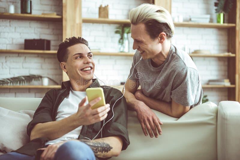 Kerels die hoofdtelefoons delen en op grappige ogenblikken van video op smartphone lachen royalty-vrije stock foto's