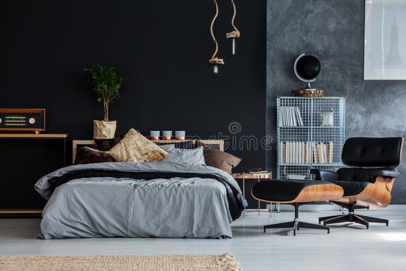 Kerelslaapkamer met chaise zitkamer stock afbeeldingen