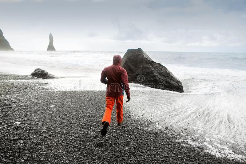 Kereltoerist die op het strand in IJsland, vrijheidsconcept lopen stock afbeeldingen