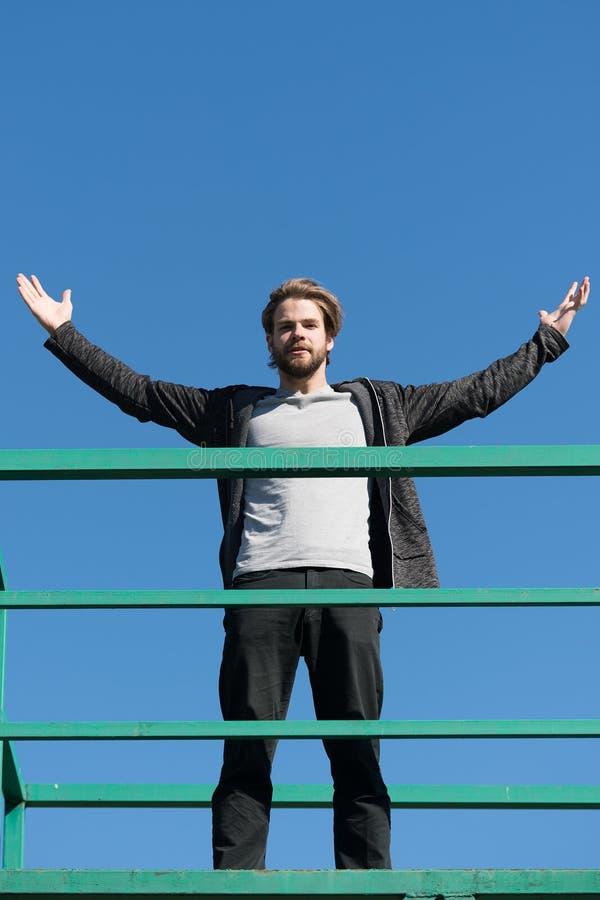 Kereltribune hoog op dakterras op blauwe hemel Gebaarde mens met opgeheven handen op zonnige openlucht Succes en toekomstig conce royalty-vrije stock afbeeldingen