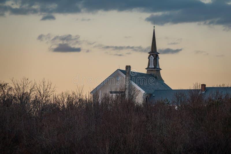 Kerk door het lange gras bij zonsondergang royalty-vrije stock foto's