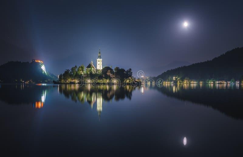 Kerk en Afgetapt Kasteel op Afgetapt Meer in Slovenië bij Nacht stock foto's
