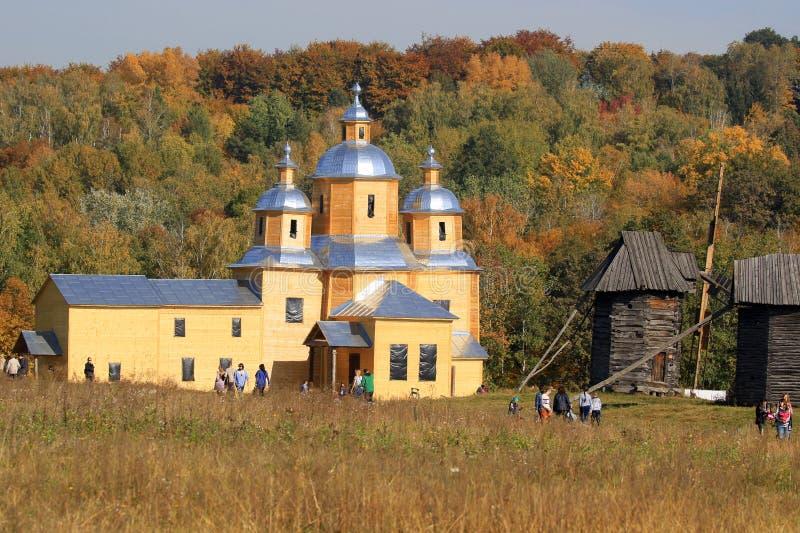 Kerk en groep oude houten windmolens die zich op de weide bevinden royalty-vrije stock foto's