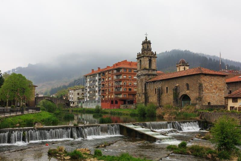 Kerk met rivier en waterval in voorgrond van Balmaseda royalty-vrije stock afbeelding