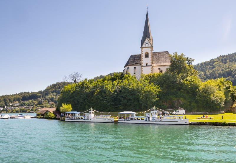 Kerk met toeristenboten op Worthersee in Maria Worth, Carinthi stock fotografie