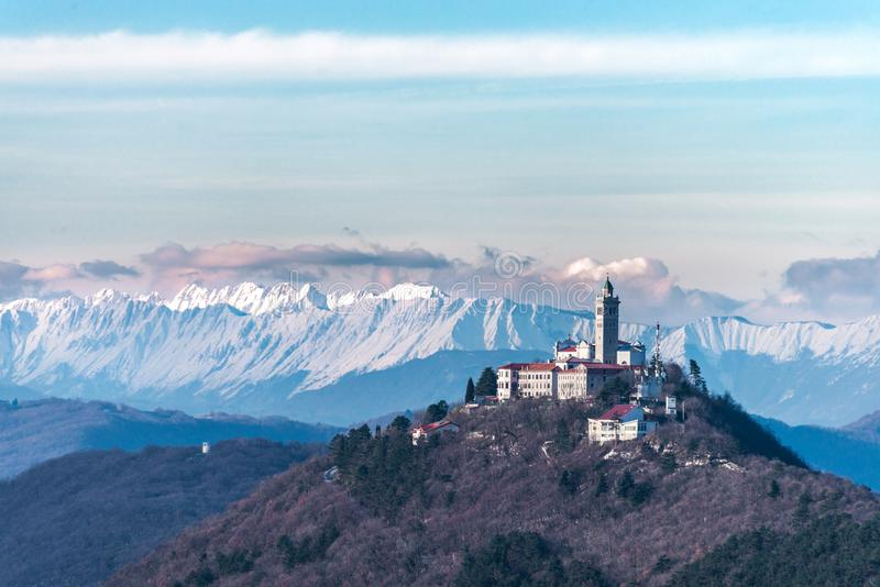 Kerk op heuvel met de alpen op de achtergrond stock foto