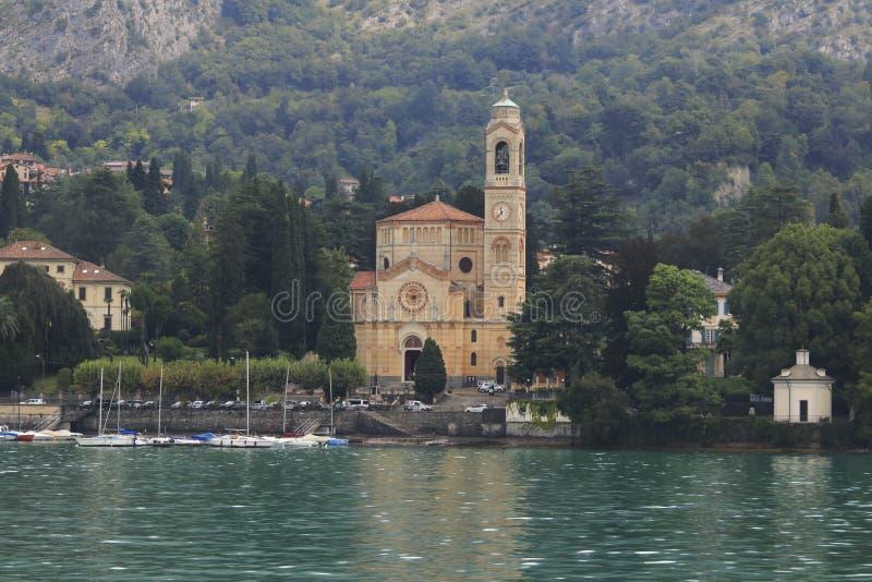 Kerk San Lorenzo met haven in Tremezzo Cadenabbia met bankpromenade in Meer Como stock foto's