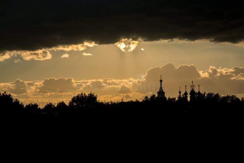 Kerk tegen de zonsonderganghemel van de brandende zon stock fotografie