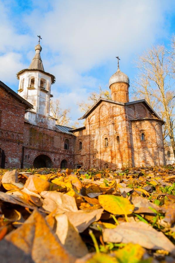 Kerk van de Aankondiging bij de Markt en de klokketoren in Veliky Novgorod, Rusland De mening van de herfst Oranje bladeren op ze royalty-vrije stock foto