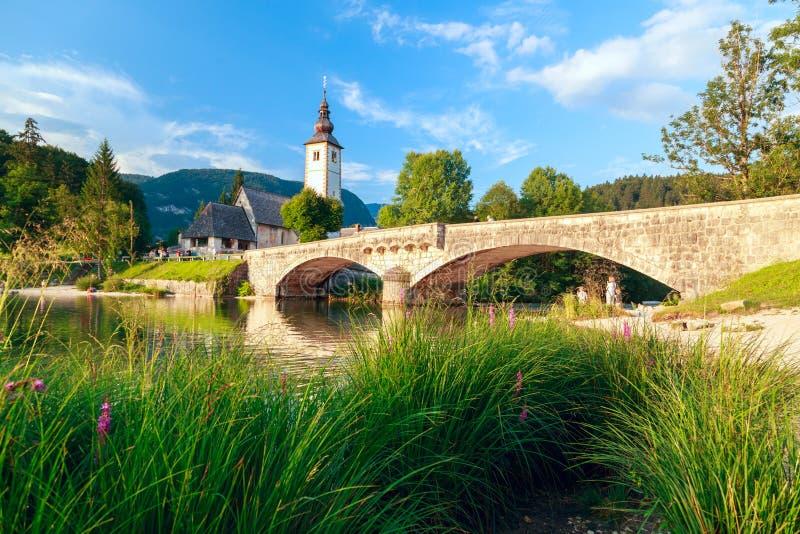 Kerk van SV John Doopsgezind en een brug door het Bohinj-meer royalty-vrije stock fotografie
