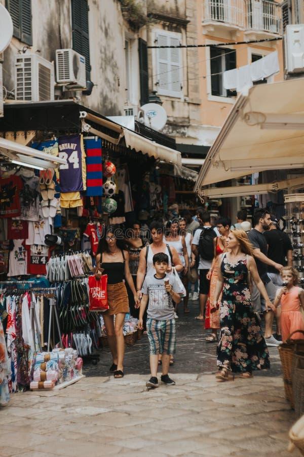 KERKYRA CORFÚ, GRECIA - 9 de junio de 2018: Muchedumbre de gente en la calle turística con las tiendas de souvenirs en el centro  fotos de archivo