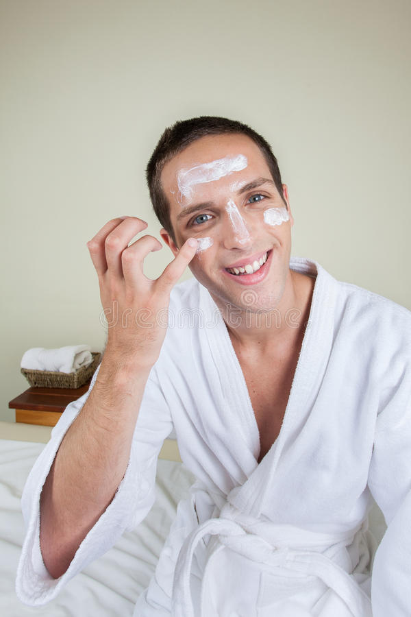 Kerl, der auf Gesichtscreme sich setzt lizenzfreie stockfotos