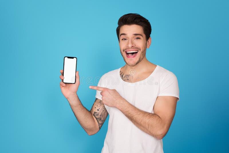Kerl, der auf Smartphone mit leerem Bildschirm zeigt stockfotografie