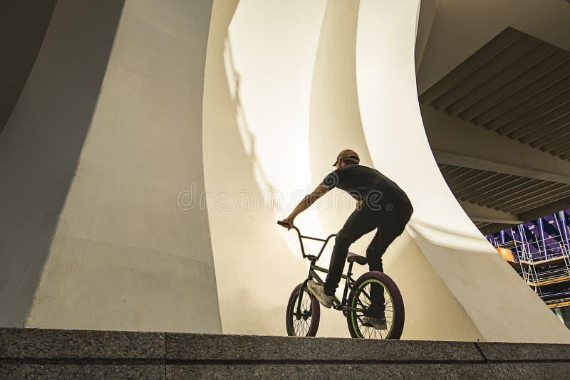 Kerl, der ein bmx Fahrrad auf die Straße reitet Freistil BMX in der Stadt stockfotos
