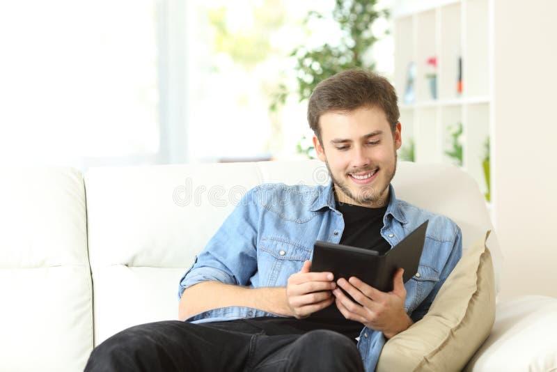 Kerl, der ein Buch in einem ebook Leser liest lizenzfreie stockfotos