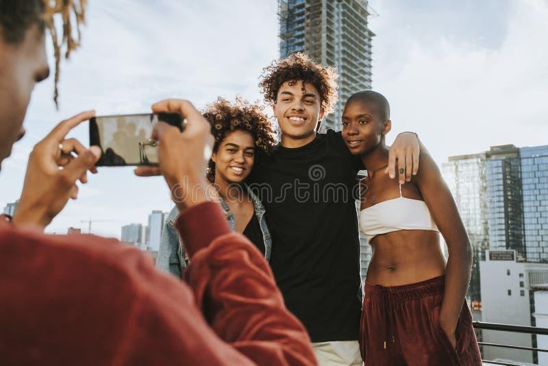 Kerl, der ein Foto seiner Freunde an einer Dachspitze macht lizenzfreies stockfoto