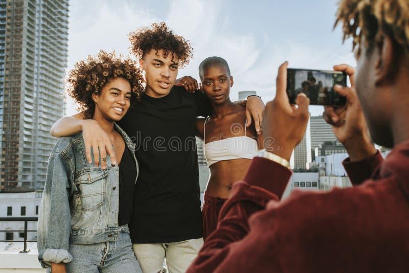 Kerl, der ein Foto seiner Freunde an einer Dachspitze macht lizenzfreies stockbild