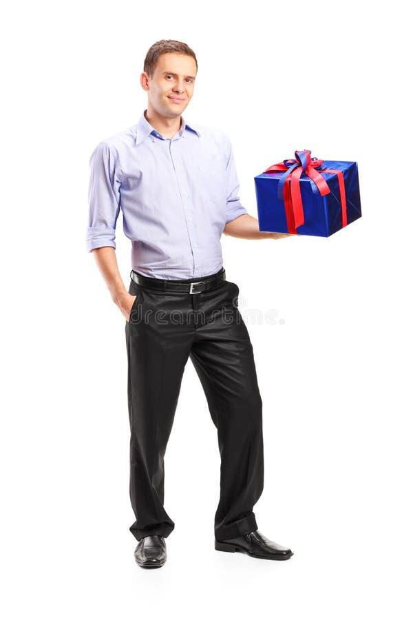Kerl, der ein großes Geschenk hält stockbilder