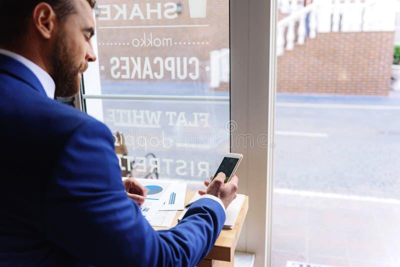 Kerl, der in einem Café mit Telefon stillsteht stockfotografie