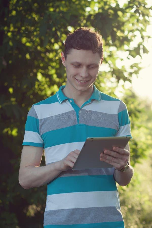Kerl, der einen Tabletten-PC verwendet stockbild