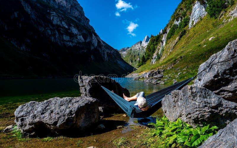 Kerl, der in einer Hängematte zwischen zwei Steinen an einem Gebirgssee enjoing ist die Ansicht kühlt stockbild