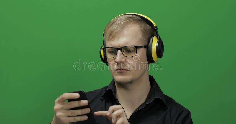 Kerl, der intelligentes Telefon in den drahtlosen gelben Kopfh?rern verwendet Gr?ner Bildschirm stockfotos