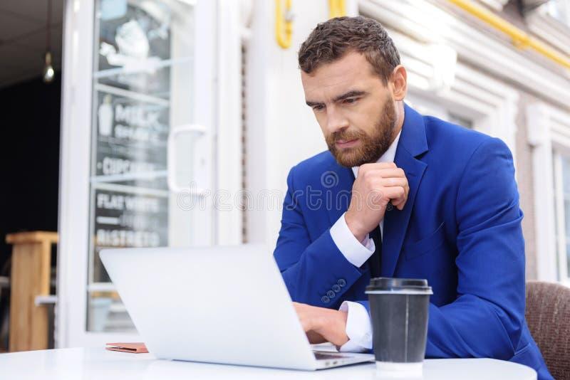 Kerl in der Klage, die vor Laptop sitzt stockbild
