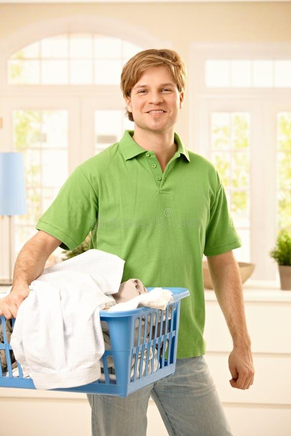 Kerl, der Kleidung zur Wäsche nimmt stockfotografie