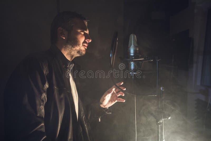Kerl, der mit einem mic auf einem Stadium singt Musiker und Sänger lizenzfreies stockbild