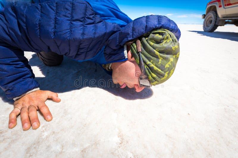 Kerl, der Salz Oberflächen-Salar de Uyuni-Wüste, Bolivien leckt lizenzfreies stockfoto