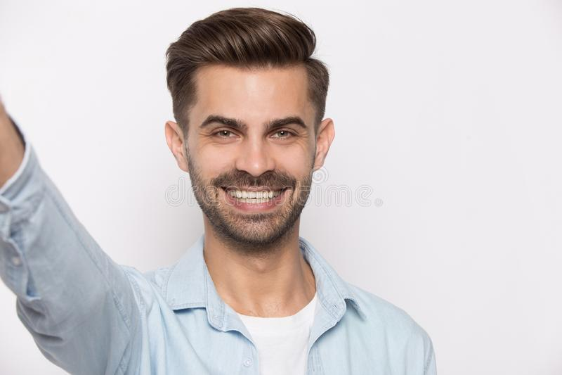 Kerl, der Smartphoneansicht von der Web-Kamera lokalisiert auf Weiß verwendet stockfotografie