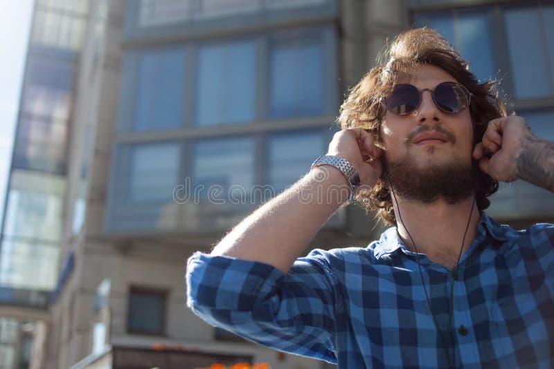 Kerl in der Sonnenbrille die Musik genießend Porträt des jungen hübschen stilvollen Mannes auf der Straße lizenzfreie stockbilder