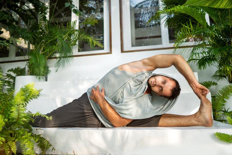 Kerl, der Yoga im Dschungel tut und Spalten tut lizenzfreie stockfotografie