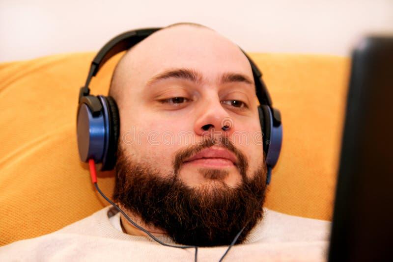 Kerl, der zu Hause Musik auf Ihrer Tablette hört lizenzfreie stockfotos