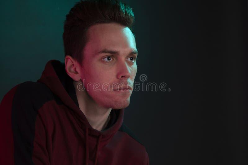 Kerl in einem mit Kapuze Sweatshirt, das im Studio aufwirft, ohne die Kamera zu betrachten lizenzfreies stockfoto