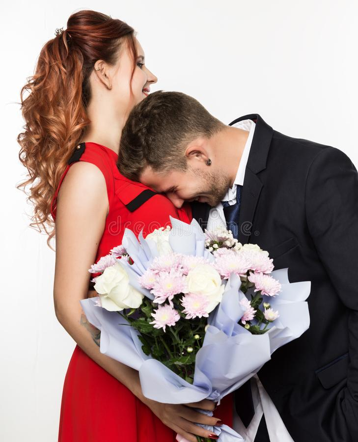 Kerl gab einer Freundin auf einem Datum einen Blumenstrauß Verbinden Sie Sitzung für Datum an einem hellen Hintergrund stockfotografie
