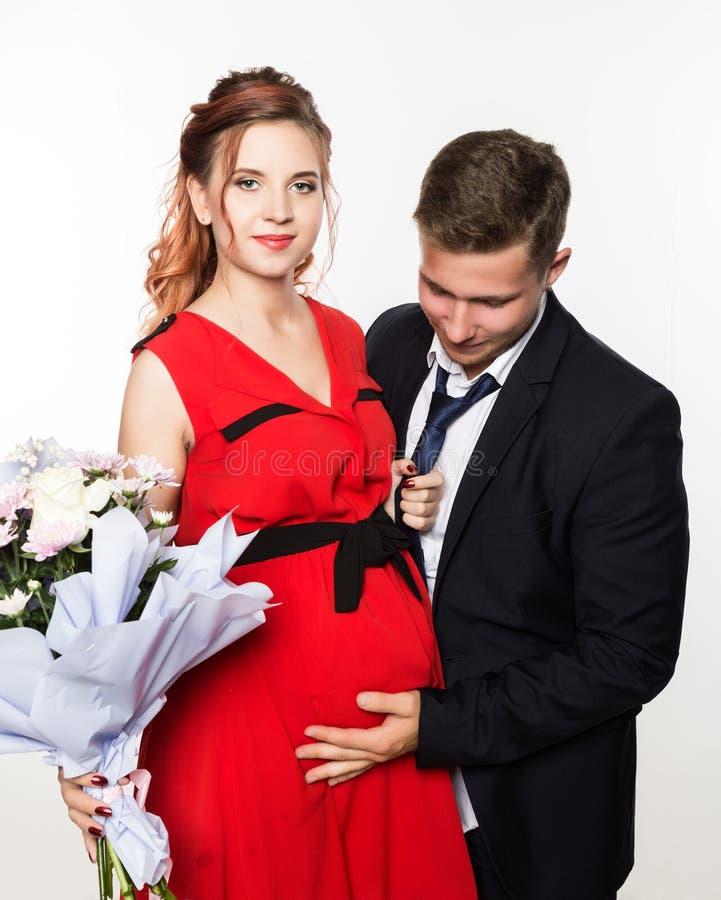 Kerl gab einer schwangeren Freundin auf einem Datum einen Blumenstrauß Verbinden Sie Sitzung für Datum an einem hellen Hintergrun lizenzfreie stockfotos