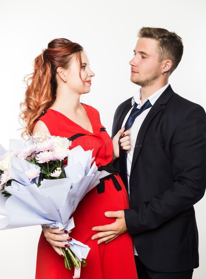 Kerl gab einer schwangeren Freundin auf einem Datum einen Blumenstrauß Verbinden Sie Sitzung für Datum an einem hellen Hintergrun stockfoto