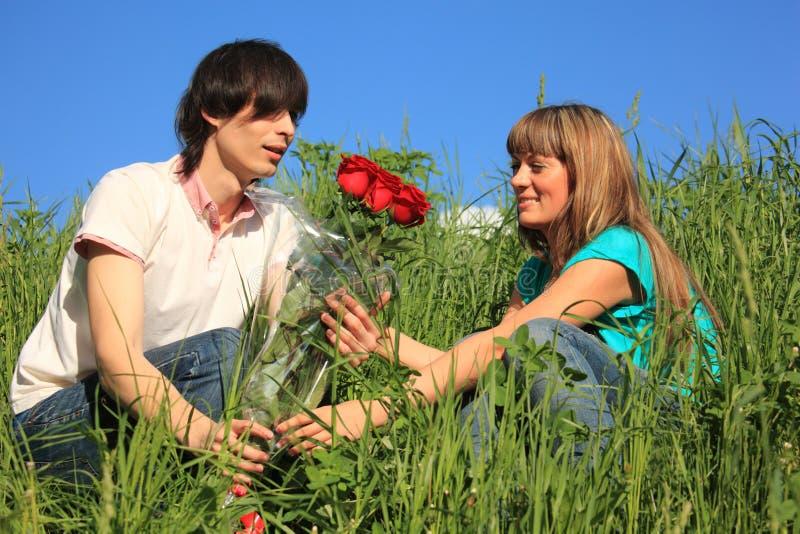 Kerl gibt zum Mädchenblumenstrauß der Rosen lizenzfreie stockbilder
