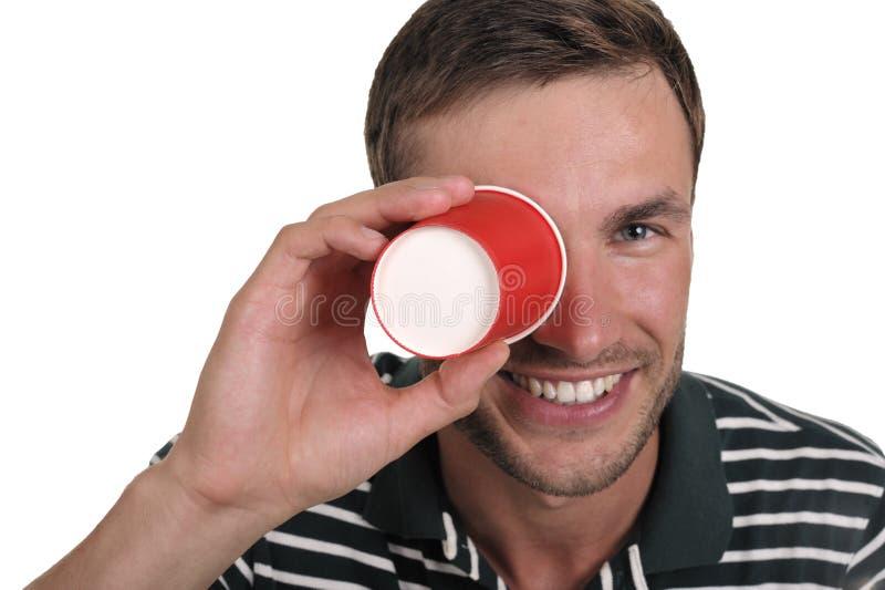 Kerl hält ein Papierglas in einer Hand an stockbild