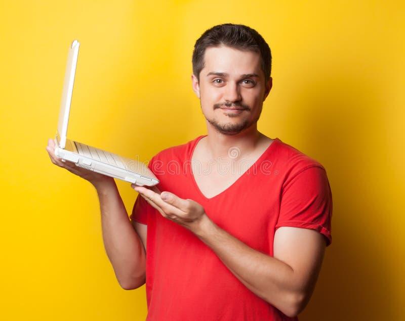 Kerl im T-Shirt mit Laptop-Computer stockfoto